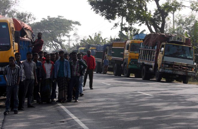 Drivers of goods laden trucks anxiously 'wait for their turn' near their vehicles a little away from the 'extortionist' law enforcers at Gharinda Bypass point on Dhaka-Tangail Highway on Tuesday afternoon. PHOTO: STAR