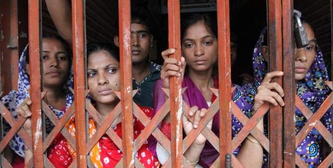 This August photo shows female workers standing behind the collapsible gate of a factory owned by the Tuba Group in Badda of the capital. Police padlock the entrances of the factory so that the workers could not go out of the factory. Photo: Star