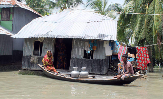 A tidal surge affected family of Lalua union in Kalapara upazila of Patuakhali collects fresh drinking water from a distant village by boat yesterday. Photo: Star