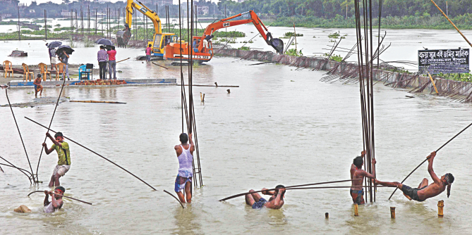 A LAUGHABLE EFFORT … A few workers try to wiggle iron rods while two small diggers find it difficult to reach the illegal wall an encroacher built in the river Turag. Such was the poor effort the BIWTA offered to recover the river near Kamarpara Bridge yesterday. The authorities did nothing while the occupier was building the structures.  Photo: Rashed Shumon