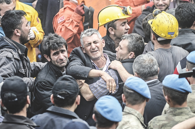 Miners react as bodies of their dead co-workers are carried out of the mine. Photo: AFP