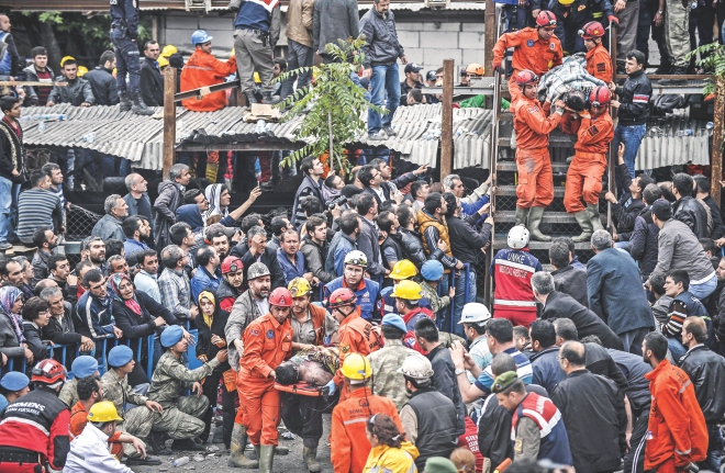 Tragedy a mile underground:  Rescuers carry out dead miners yesterday after an explosion and fire in a coal mine in the western Turkish province of Manisa killed at least 245 people and 120 remain trapped underground.  Photo: AFP