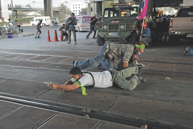 A Thai anti-government protester aims his gun and shoot towards. Thai pro-election protesters (not seen) during clashes in Bangkok, yesterday.   Photo: AFP