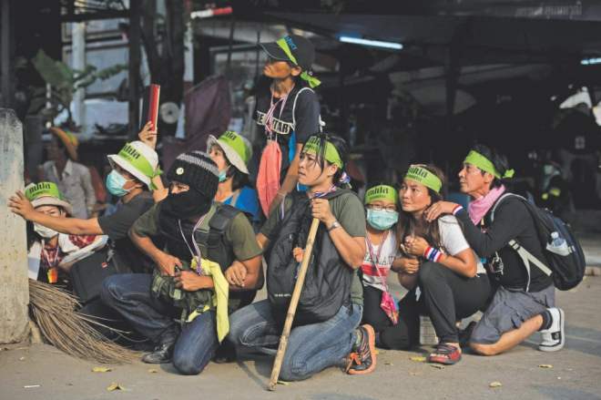 Anti-government protesters take cover during the clashes. Photo: AFP
