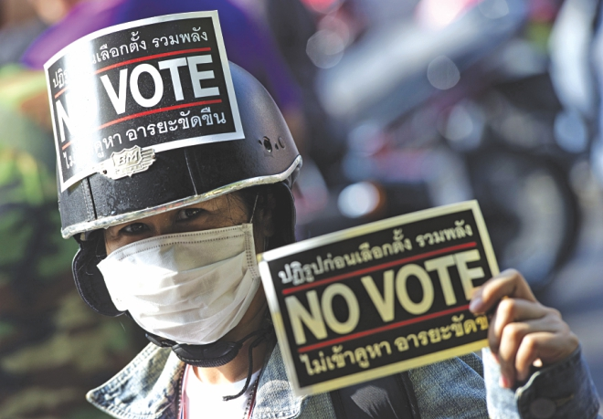 A protester holds a protest placard urging not to vote. Photo: AFP