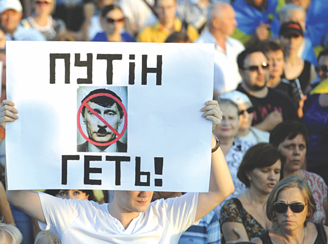 A Ukrainian man holds a placard reading 'Putin get out!' during a rally in the center of the southern Ukrainian city of Mariupol, yesterday. Photo: AFP