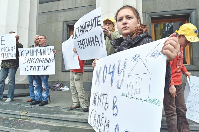 Refugees from Crimea and eastern Ukrainian regions hold placards reading (L-R)  Stop Putin!, I want to live in my house!, 'Legal status for Crimean' during a rally to demand a legal legislation of their status in front of the Ukrainian parliament in Kiev yesterday. Photo: AFP