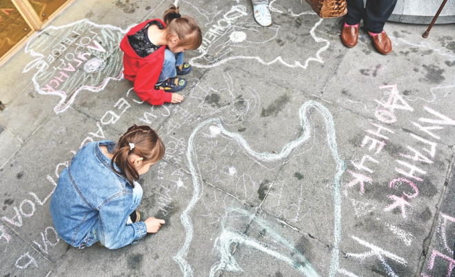 Refugee children draw symbolic maps depicting their regions and cities, on the sidewalk at the entrance of the parliament during the rally. At least 10,000 people have been driven from their homes since the start of the Ukraine crisis, with Crimean Tatars the hardest-hit, according to the UN. Photo: AFP