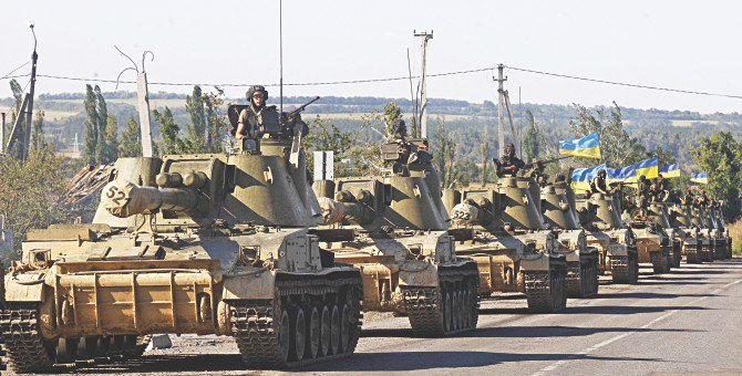 A column of Ukrainian tanks travels in Donetsk region yesterday. Beleaguered Ukrainian President Petro Poroshenko announced that he and his Russian counterpart Vladimir Putin had agreed a surprise truce in Ukraine's four-month war with pro-Moscow rebels. Photo: AFP