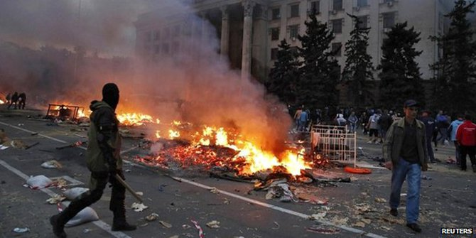 A protester walks past a burning pro-Russian tent camp near the trade union building in Odessa - 2 May 2014 Reports suggest that both pro-Russians and supporters of Kiev were throwing petrol bombs in the area
