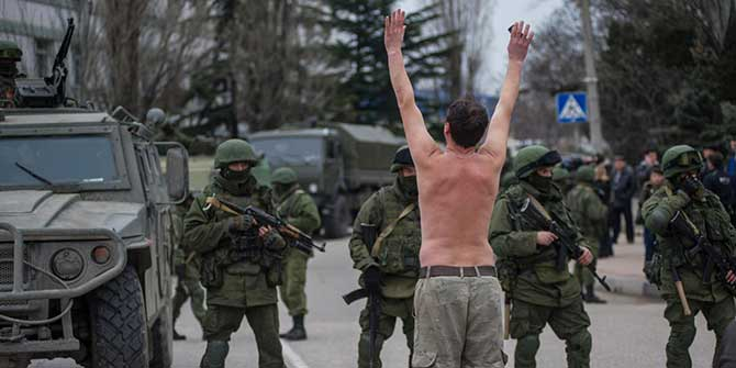 A Ukrainian man stands in protest in front of gunmen in unmarked uniforms as they stand guard in Balaklava, on the outskirts of Sevastopol, Ukraine, Saturday, March 1. Photo: AP