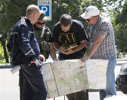 Ukrainian Ministry Emergency officer, left, Donetsk People's Republic fighter, 2nd left, and members of the OSCE mission in Ukraine examine a map as they discuss the situation around the site of the crashed Malaysia Airlines Flight 17 in the city of Donetsk, eastern Ukraine July 27.