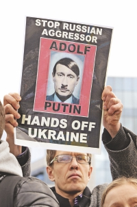 An anti-war demonstrator holds a sign depicting Russian President Vladimir Putin as World War II Nazi German dictator Adolf Hitler as he takes part in a protest against Russian intervention in Ukraine, on the sidelines of a EU Foreign Affairs Ministers meeting dedicated to the situation in Ukraine at the EU Council building in Brussels, yesterday.  Photo:AFP