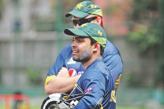 Pakistan star Umar Akmal watches his teammates training at the Sher-e-Bangla National Stadium in Mirpur yesterday, ahead of today's big clash against India. PHOTO: FIROZ AHMED