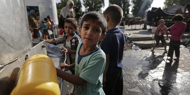 Displaced Palestinian children collect water at the Abu Hussein UN school, in Jebaliya refugee camp, northern Gaza Strip, 30 July 2014 The UN school hit on Wednesday was sheltering more than 3,000 displaced Palestinians. Photo: AP