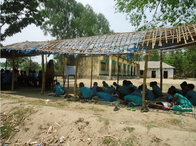Students of Rajagaon Government Primary school at Rajagaon village in Thakurgaon Sadar upazila attend classes under a makeshift shed as the school building was declared abandoned in June last year after cracks developed on its walls and floors. Photo: Star