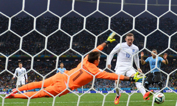 England's forward Wayne Rooney (L) scores against Uruguay's goalkeeper Fernando Muslera (L) during a Group D football match between Uruguay and England at the Corinthians Arena in Sao Paulo during the 2014 FIFA World Cup on June 20, 2014. Photo: Getty Images