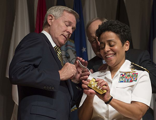 Admiral Michell Howard helps Secretary of the Navy Ray Mabus to put four-star shoulder boards on Howard's service white uniform during her promotion ceremony at the Women in Military Service for America Memorial. Photo: US Navy