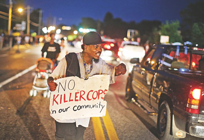 A semonstrator hold a placard to protest the shooting death of Michael Brown Ferguson, Missouri, on Thursday. Violent protests have erupted along West Florissant in Ferguson each of the last four nights as demonstrators express outrage over the shooting death of Michael Brown by a Ferguson police officer on August 9.  Photo: AFP