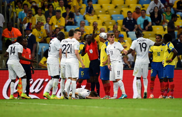 Referee Noumandiez Doue (C) calls a stretcher as Lucas Digne of France lies injured after a challenge by Antonio Valencia (2nd R) of Ecuador during the 2014 FIFA World Cup Brazil Group E match between Ecuador and France at Maracana on June 25, 2014 in Rio de Janeiro, Brazil. Photo: Getty Images