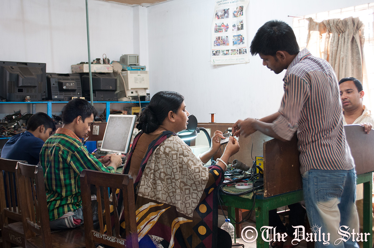 Jhorna Rani Nath, the electronics instructor at CRP, teaches Uzzal Das on electronic equipment repair. Three Rana Plaza survivors are at present taking the course. Photo: Moyukh Mahtab