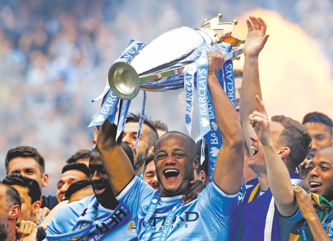 Manchester City's Belgian captain Vincent Kompany hoists the English Premier League trophy after beating West Ham United on the title-deciding final day at the Etihad Stadium yesterday. Photo: Reuters