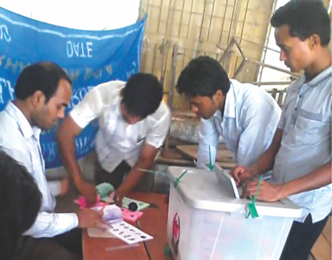 Supporters of Awami League-backed candidates cast fake votes taking ballot papers from Assistant Presiding Office Bikash Chandra Das at Kolakopa Govt Primary School polling centre in Daulatkhan upazila of Bhola at 9:45am Sunday. About 60-70 people actually cast their votes there but the results show 1,026 votes cast and the ruling Awami League-backed candidate got 921 of them. Photo: Md Zakir Hossain