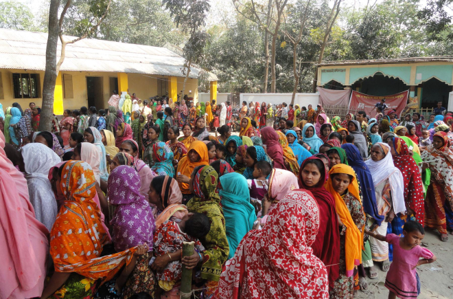 Women voters of Kornai village, who could not cast their votes in the January 5 parliamentary polls due to violence unleashed by BNP and Jamaat-Shibir men, wait in queues in front of Kornai Government Primary School polling centre under Dinajpur Sadar upazila yesterday. Photo: Star