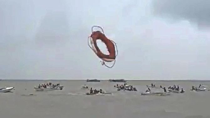 This image taken from a video captured by an eyewitness shows a lifebuoy of a passing ferry being thrown into the Padma where people on speedboats were trying to pull passengers of Pinak-6 out of the water moments after it sank.  Photo: Video Grab