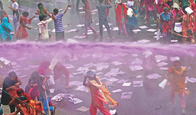 Police use a water cannon to disperse garment workers of five factories of Tuba Group, the parent company of Tazreen Fashions Ltd, in front of Hossain Market of the capital's Badda yesterday. The workers blocked Kuril Bishwa Road for half an hour, demanding arrears of two months and the salaries of the first 15 days of the current month in addition to the Eid bonus. Police also charged batons, leaving at least 10 demonstrators injured. Photos: Courtesy
