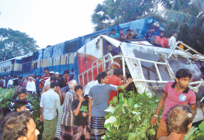 The wrecked bus on its side after Simanta Express from Saidpur rammed it at Barobazar level crossing, about 12 miles from Jessore, and dragged it half a kilometre, killing 11 people returning from a wedding early yesterday.  Photo: Azibor Rahman