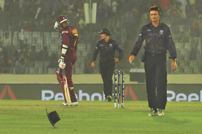 The hat of umpire Rod Tucker (R) is sent for a ride by strong wind, which was followed by hailstorm and heavy rain, during the ICC World Twenty20 first semifinal between Sri Lanka and the West Indies at Sher-e-Bangla National Stadium in Mirpur yesterday. PHOTO: FIROZ AHMED