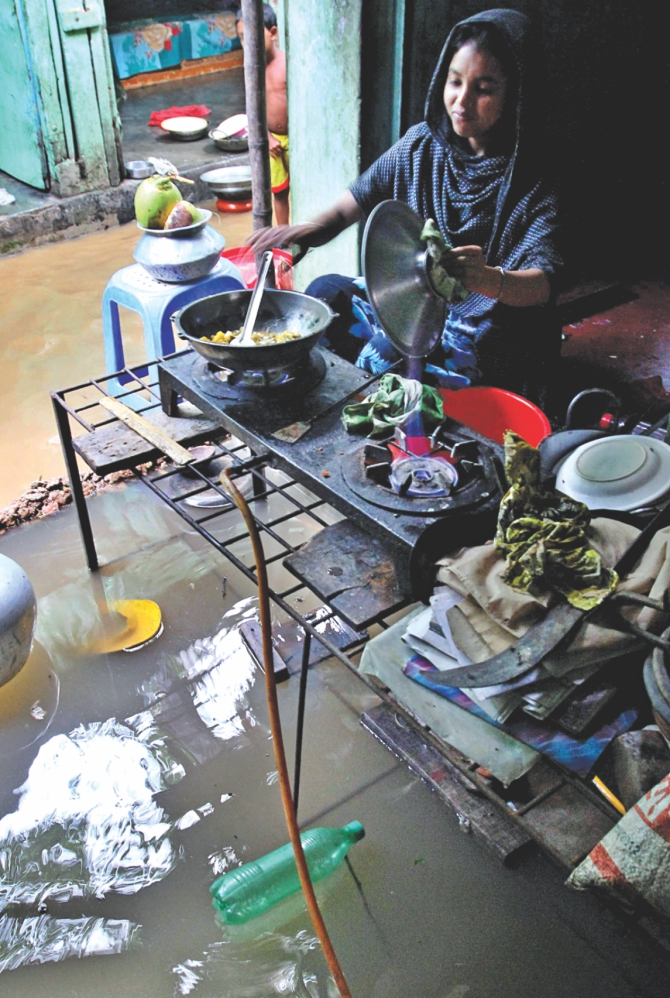 A woman cooks in her kitchen, that had been flooded. Photo: Anisur Rahman