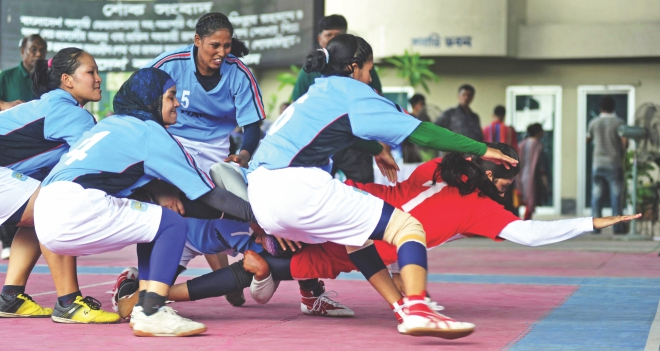 Dhaka players pounce on a Narail raider during the final of the Inter-District Women's Kabaddi Championship at the Volleyball Stadium in Paltan yesterday. PHOTO: STAR