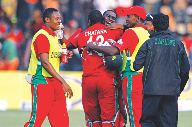Zimbabwe captain Elton Chigumbura is mobbed by his teammates after their famous three-wicket win against Australia at the Harare Sports Club yesterday. It was Zimbabwe's first ODI victory against the Aussies after 31 years. Photo: AFP