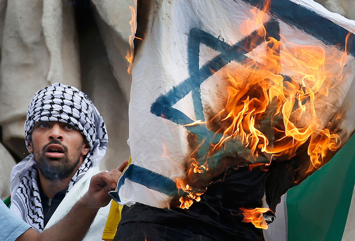 Pro Palestinian protester burns an Israeli flag during demonstration banned by police, in support of Gaza in central Paris, July 26, 2014. Photo: Reuters