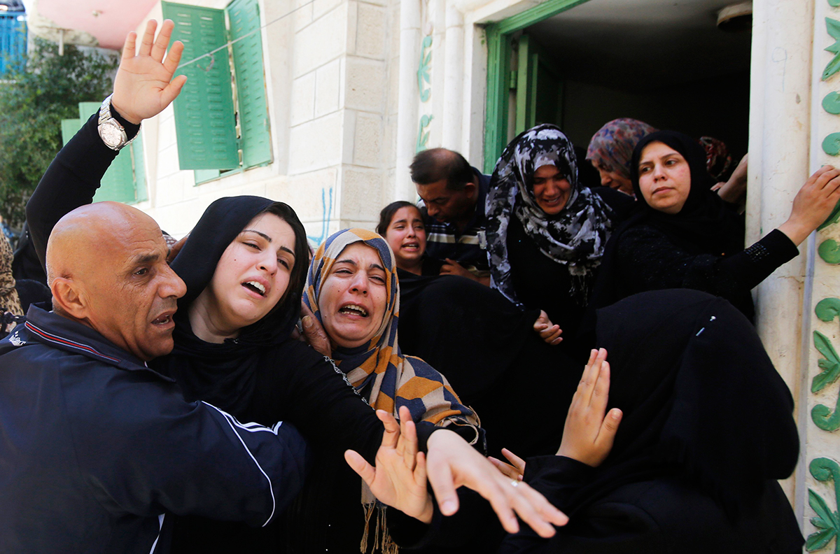 The wife (L) of Palestinian Eid Rabah Fdilat, whom medics said was killed during clashes with Israeli troops on Friday, mourns during his funeral in Arroub refugee camp, north of the West Bank city of Hebron July 26, 2014. Photo: Reuters