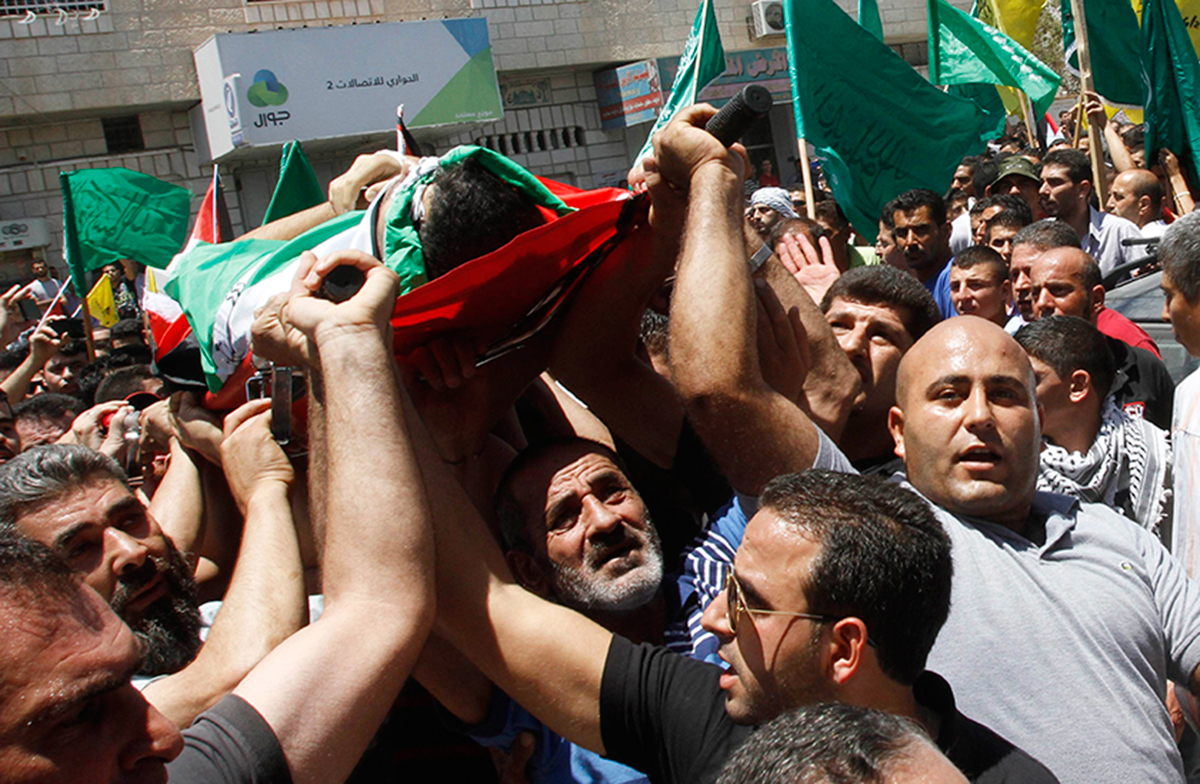 Palestinians carry the body of Tayyeb Shehada, whom medics said was killed during clashes with Israeli troops on Friday, during his funeral in the West Bank town of Hawara near Nablus July 26, 2014. Photo: Reuters