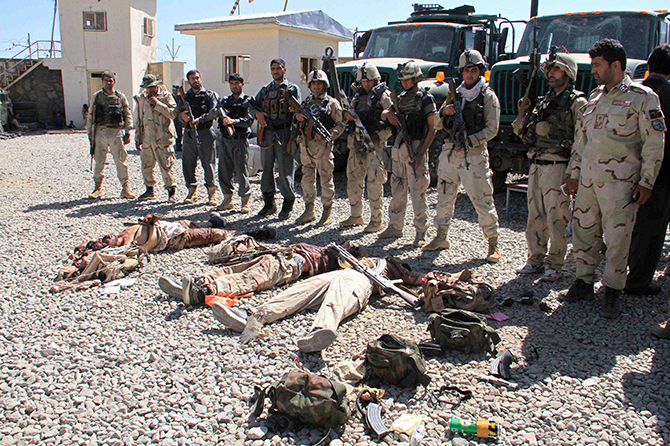 Afghan security forces gather around the bodies of dead Taliban insurgents at the site of a suicide attack in Ghazni Province September 4, 2014. Photo: Reuters