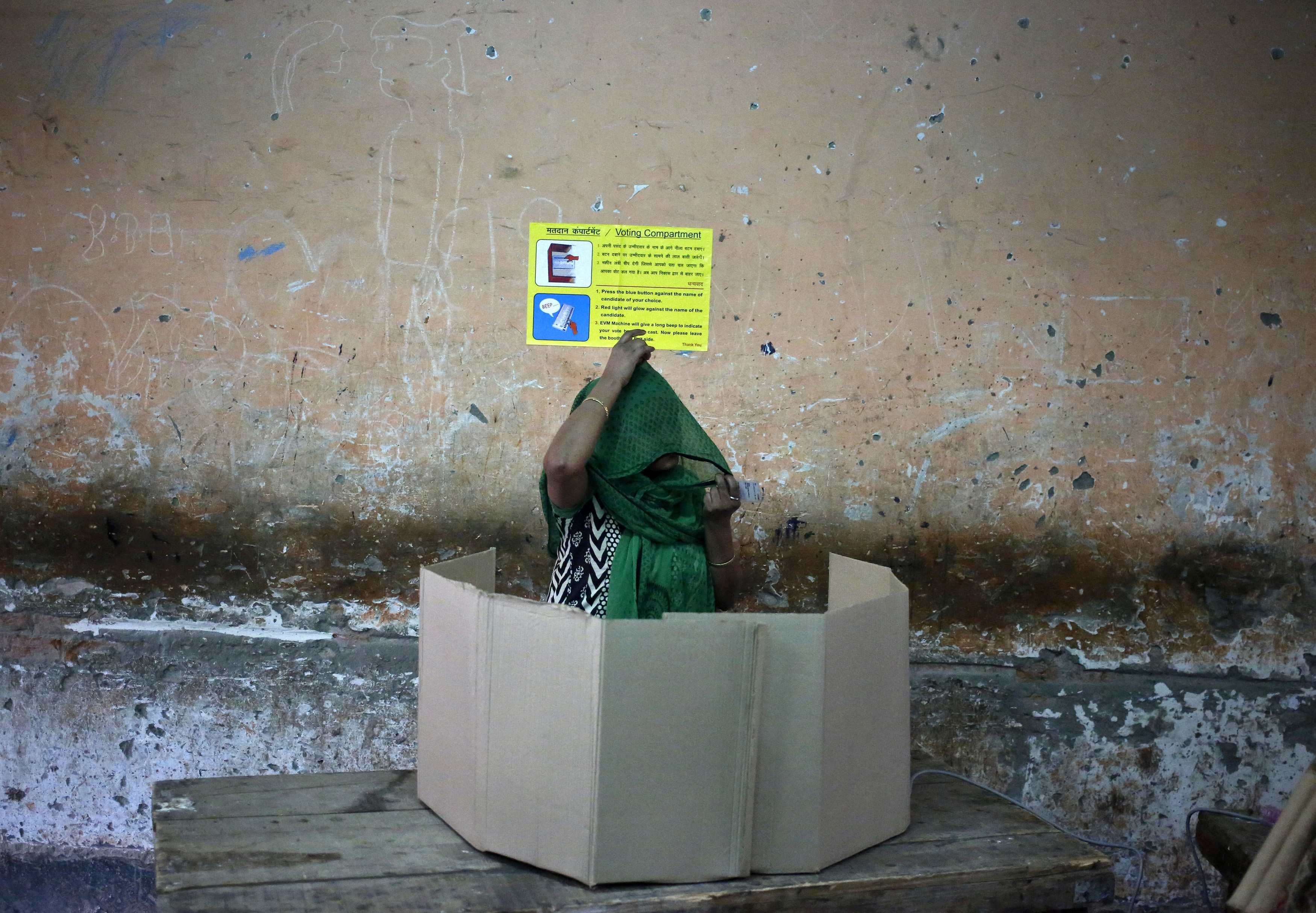 1.A voter prepares to cast her vote at a polling station during the state assembly election in New Delhi February 7, 2015. Photo: Reuters