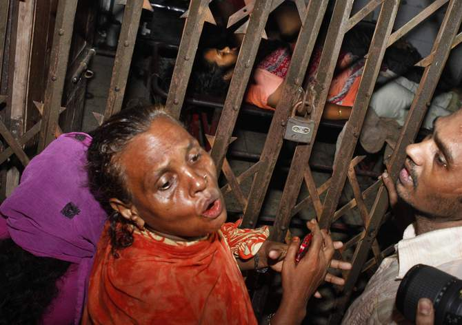 Relatives of three victims, who were shot dead, at Sonalibagh burst into tears in front of a room of Dhaka Medical College and Hospital where the bodies were kept on Thursday. Photo: STAR