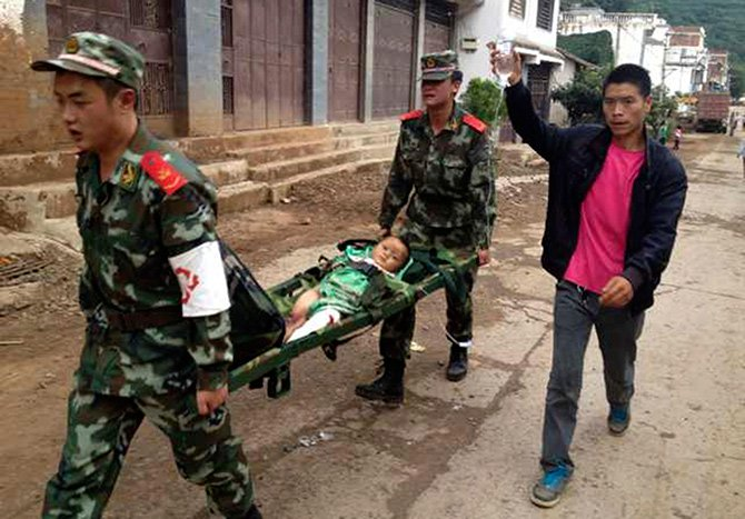 Paramilitary policemen carry an injured child on a stretcher as they carry out rescue operations after an earthquake hit Longtoushan township of Ludian county, Yunnan province August 3, 2014. Photo: Reuters