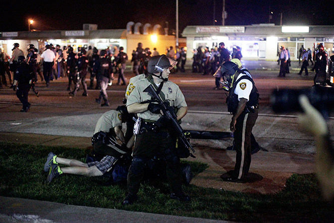Police detain a demonstrator during a protest against the shooting death of Michael Brown in Ferguson Missouri August 18, 2014. Police fired tear gas and stun grenades at protesters on Monday after days of unrest sparked by the fatal shooting of unarmed black teenager Michael Brown by a white policeman.Photo: Reuters
