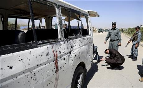 Afghan security personnel investigate a damaged vehicle after it was hit by a remote-controlled bomb on the outskirts of Kabul, Afghanistan, Tuesday. Photo: AP