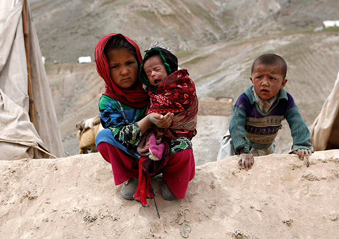Displaced Afghan children sit outside their tent near the site of a landslide at the Argo district in Badakhshan province on Sunday. The United Nations put the death toll from Friday's massive landslide in Badakhshan province, bordering Tajikistan, at up to 500. Local officials say the number killed could be as high as 2,700.  Photo: Reuters