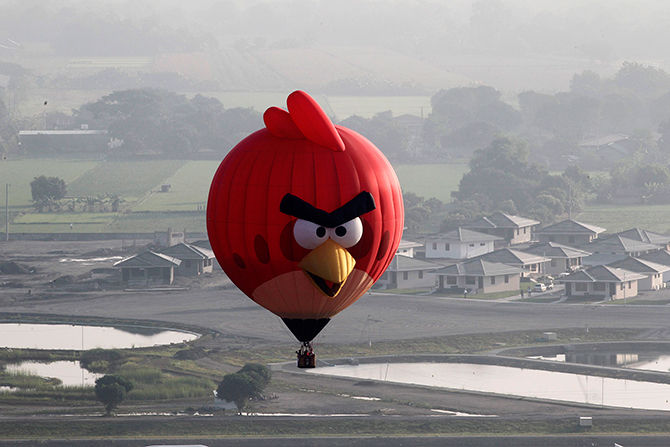 An Angry Bird inspired Hot Air balloon floats over rice fields and houses during the Philippine International Balloon festival in Lubao town, Pampanga province, north of Manila on Thursday. An estimated 30 hot air balloons participated in the event which aims to promote tourism in the Southeast Asian country, local media reported.  Photo: Reuters
