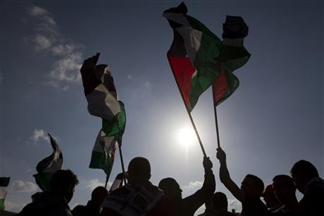 In this Friday, March 30, 2012, file photo, Arab Israeli protesters wave Palestinian flags as they gather to mark the annual Land Day event in the Arab Village of Dir Hana, northern Israel. Photo: AP