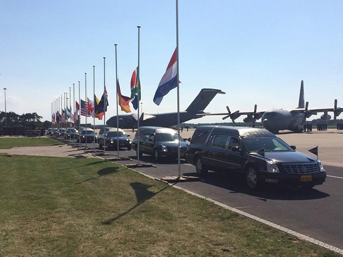 Hearses with MH17 victims coffins leave the tarmac next to the flags of the victim's nations at half-mast in the Netherlands on Wednesday, July 23, 2014. Photo taken from Twitter