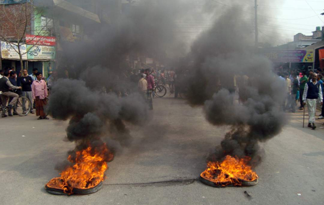 Protesters block Dianjpur-Dhaka highway by burning tyres in Nimtola area under Phulbari municipality on Wednesday. Photo: Star
