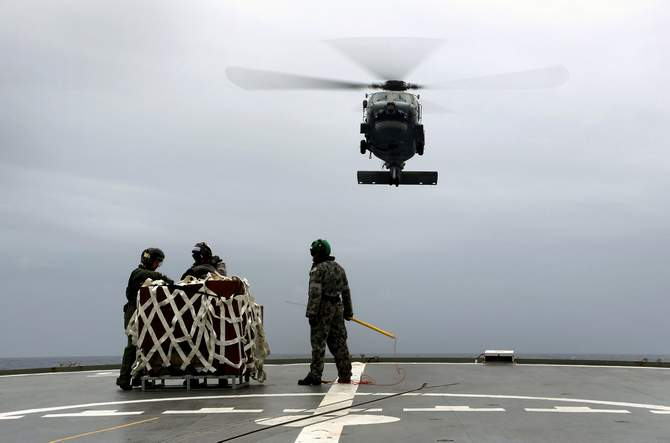 A S-70B-2 Seahawk (Tiger 75) helicopter makes an approach to the flight deck of Australian Navy ship HMAS Toowoomba to pick up supplies during a vertical replenishment at sea with HMAS Success as they continue to search for the missing Malaysian Airlines flight MH370 in this picture released by the Australian Defence Force April 6, 2014.